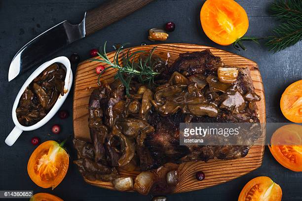 Roasted veal steak on board served with mushroom sauce viewed from above, Christmas dinner
