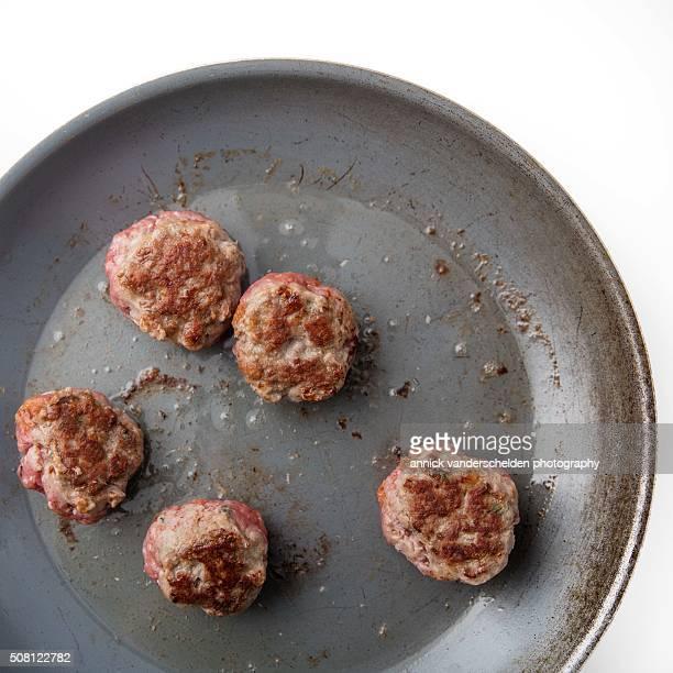 Roasting meatballs in pan.