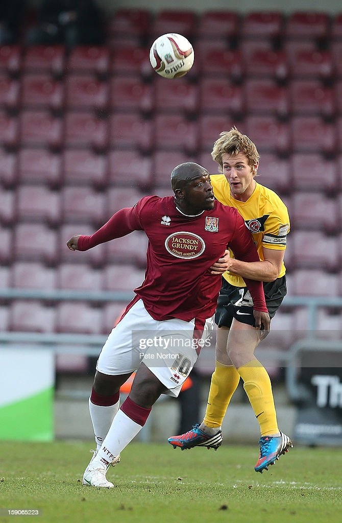 Rob Atkinson of Fleetwood Town heads the ball away from Adebayo Akinfenwa of Northampotn Town during the npower League Two match between Northampton Town and Fleetwood Town at Sixfields Stadium on January 5, 2013 in Northampton, England.