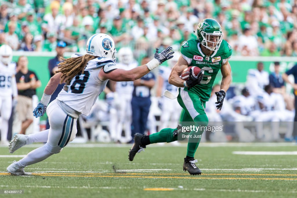 Rob Bagg #6 of the Saskatchewan Roughriders runs away from Bear Woods #48 of the Toronto Argonauts after a catch in the game between the Toronto Argonauts and Saskatchewan Roughriders at Mosaic Stadium on July 29, 2017 in Regina, Canada.
