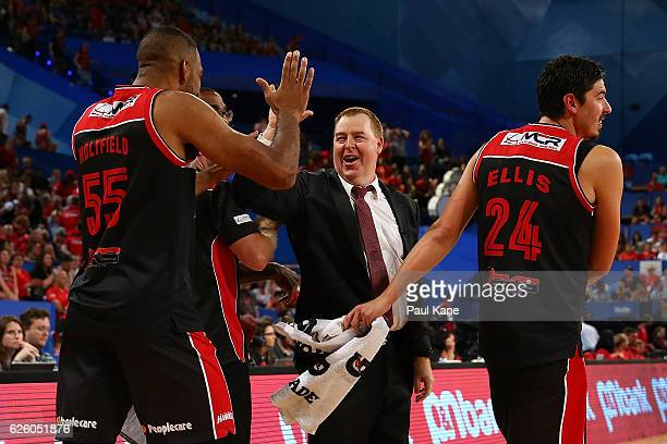 Rob Beveridge head coach of the Hawks celebrates with players after winning the round eight NBL match between the Perth Wildcats and the Illawarra...