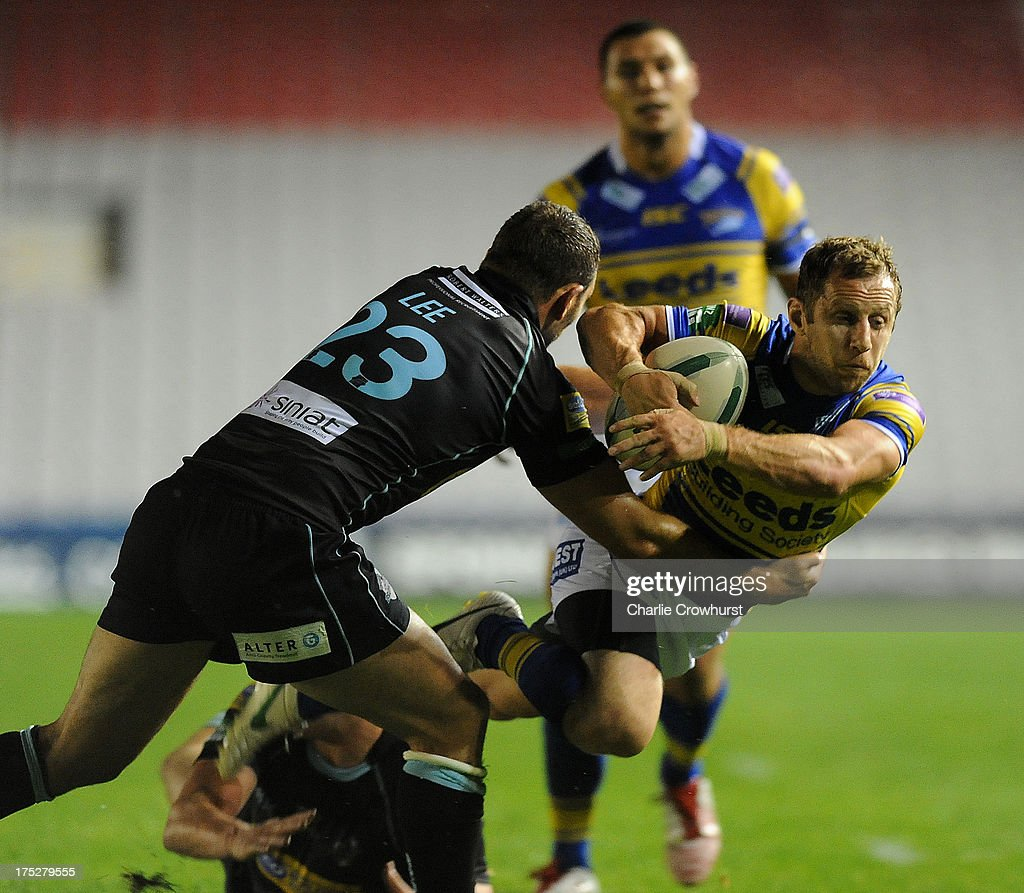 Rob Burrow of Leeds Rhinos flys through the air to avoid the tackle from London Bronco's Tommy Lee during the Super League match between London Broncos and Leeds Rhinos at Twickenham Stoop on August 01, 2013 in London, England.