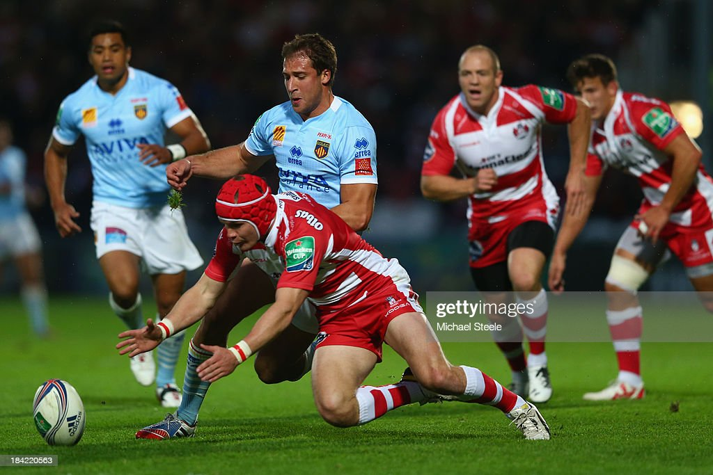 Rob Cook of Gloucester pounces on the loose ball as Tommaso Benvenuti of Perpignan closes in during the Heineken Cup Pool six match between...