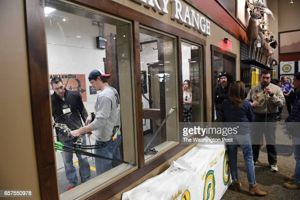 Rob Freyer left instructs Connor Duffus on using a bow and arrow in the archery range during the opening of a new Cabela's store on Thursday March 09...