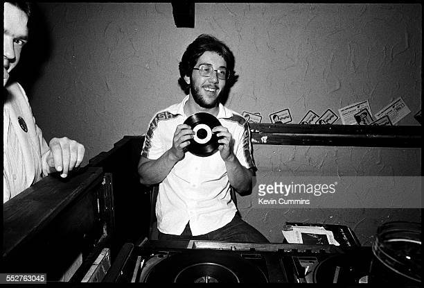 Rob Gretton manager of English rock group Joy Division holding a 45 rpm single at a club possibly Rafters in Oxford Street Manchester circa 1979