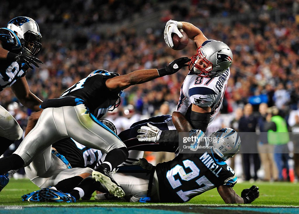 Rob Gronkowski #87 of the New England Patriots dives over Quintin Mikell #27 for a touchdown at Bank of America Stadium on November 18, 2013 in Charlotte, North Carolina. The Panthers won 24-20.