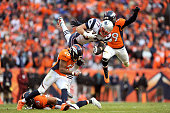 Rob Gronkowski of the New England Patriots is tackled by Josh Bush Shiloh Keo and Danny Trevathan of the Denver Broncos in the fourth quarter in the...