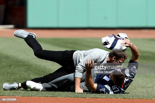 Rob Gronkowski of the New England Patriots is tackled by Tom Brady after stealing his jersey before the opening day game between the Boston Red Sox...
