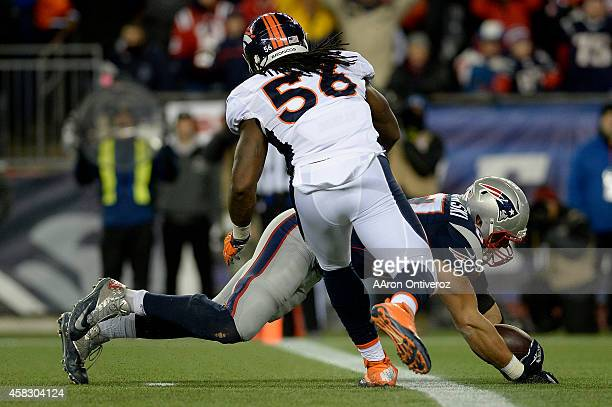 Rob Gronkowski of the New England Patriots makes a catch as Nate Irving of the Denver Broncos pursues during the second half of the Patriots' 4321...