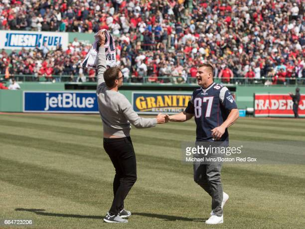Rob Gronkowski of the New England Patriots shakes hands with Tom Brady after stealing his jersey during a ceremony honoring the Super Bowl champions...