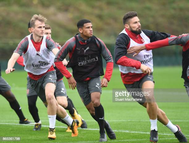Rob Holding Marcus McGuane and Olivier Giroud of Arsenal during a training session at London Colney on October 23 2017 in St Albans England