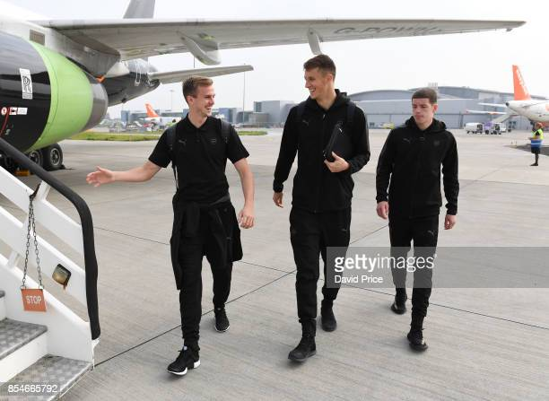 Rob Holding Matt Macey and Charlie Gilmour of Arsenal board the plane at Luton Airport on September 27 2017 in Luton England