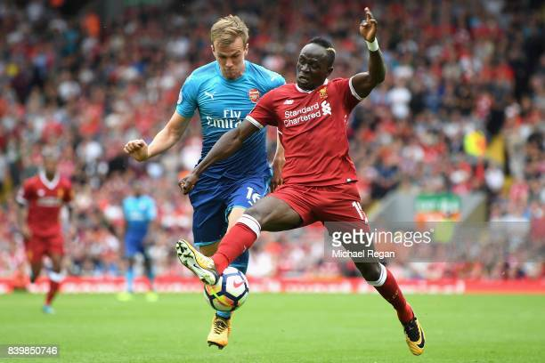 Rob Holding of Arsenal and Sadio Mane of Liverpool battle for possession during the Premier League match between Liverpool and Arsenal at Anfield on...