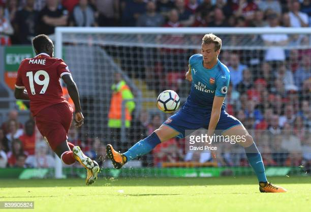 Rob Holding of Arsenal challenges Sadio Mane of Liverpool during the Premier League match between Liverpool and Arsenal at Anfield on August 27 2017...