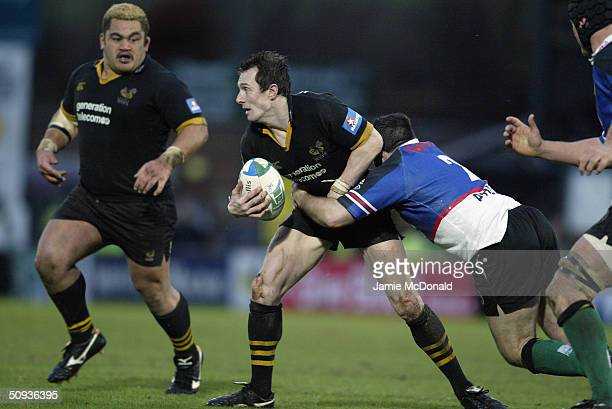 Rob Howley of Wasps looks for support as he is tackled by Mefin Davies of the Warriors during the Heineken Cup match between London Wasps and Celtic...
