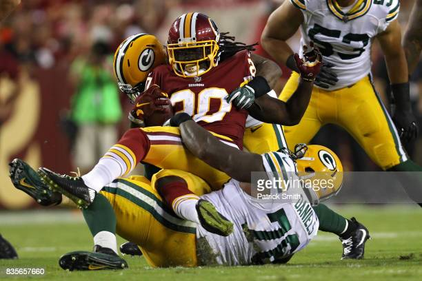 Rob Kelley of the Washington Redskins is tackled by Green Bay Packers defenders in the first half during a preseason game at FedExField on August 19...