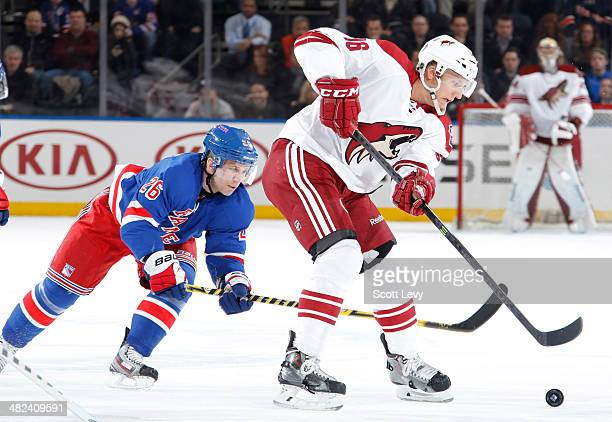 Rob Klinkhammer of the Phoenix Coyotes skates the puck past Martin St Louis of the New York Rangers at Madison Square Garden on March 24 2014 in New...