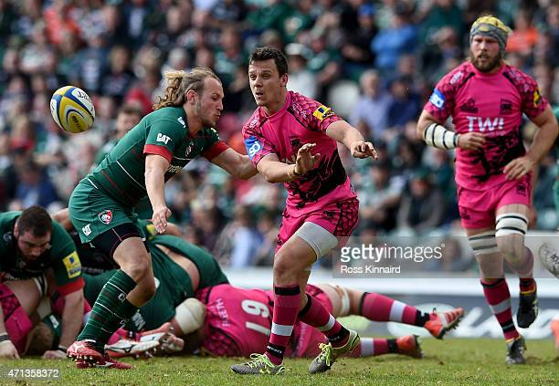 Rob Lewis of London Welsh gets his pass away under the attention of Sam Harrison of Leicester Tigers during the Aviva Premiership match between...