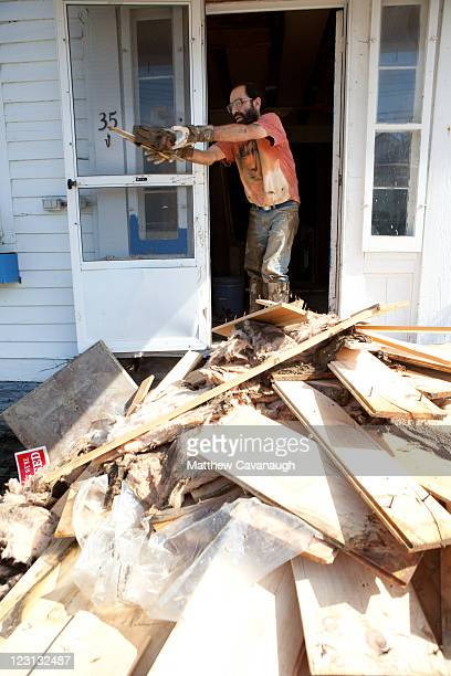 Rob Marzelli removes debris from his tile shop and home that was flooded in tropical storm Irene on West Main Street on August 31 2011 in Wilmington...