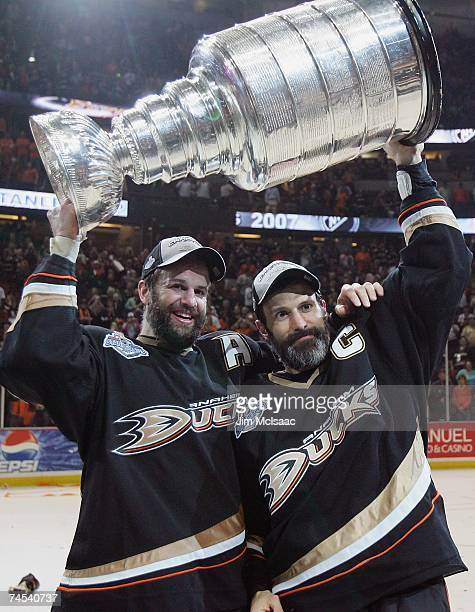 Rob Niedermayer of the Anaheim Ducks and brother Scott Niedermayer hoist the Stanley Cup after their team's victory over the Ottawa Senators in Game...