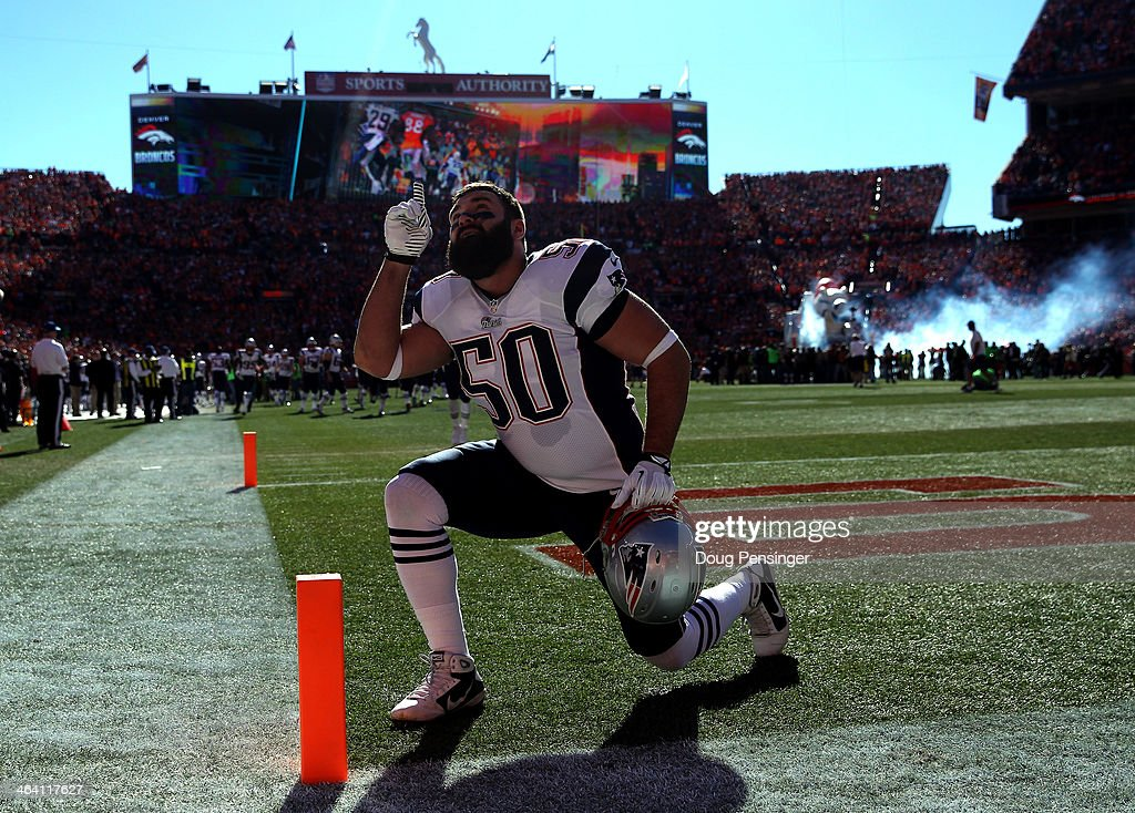 Rob Ninkovich of the New England Patriots kneels in the end zone prior to the AFC Championship game against the Denver Broncos at Sports Authority...