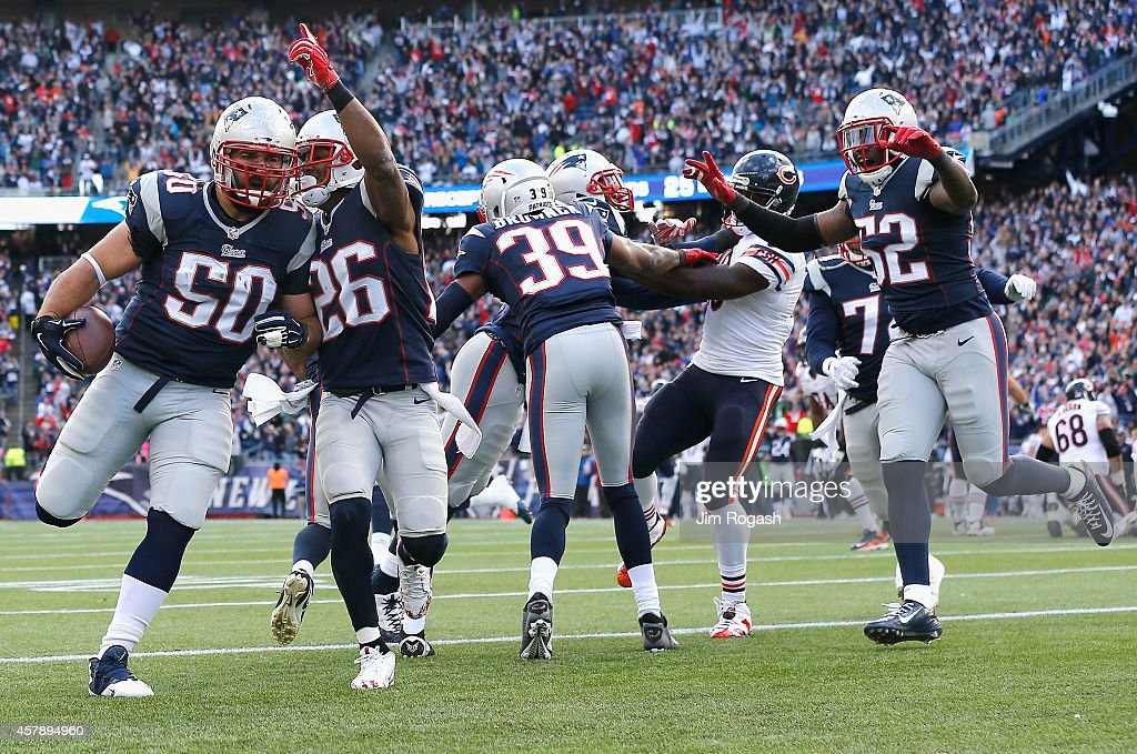 Rob Ninkovich of the New England Patriots reacts alongside Logan Ryan and Akeem Ayers after recovering a fumble and scoring a touchdown during the...
