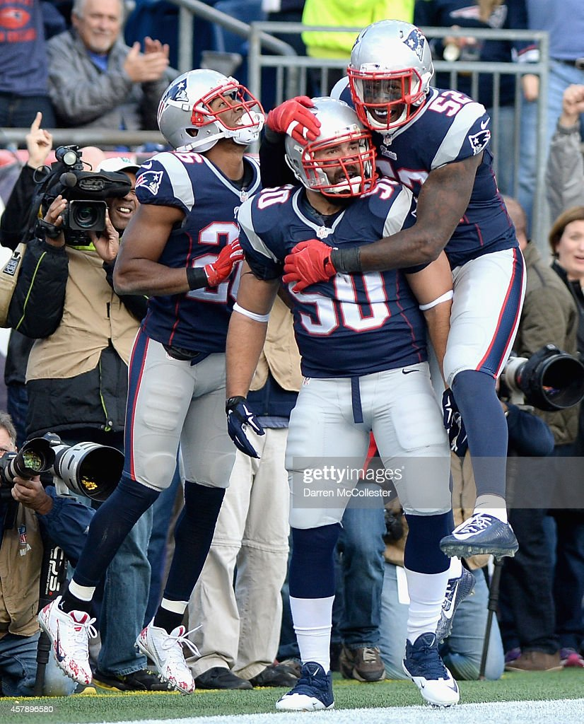 Rob Ninkovich of the New England Patriots reacts with Logan Ryan and Akeem Ayers after recovering a fumble for a touchdown during the second quarter...