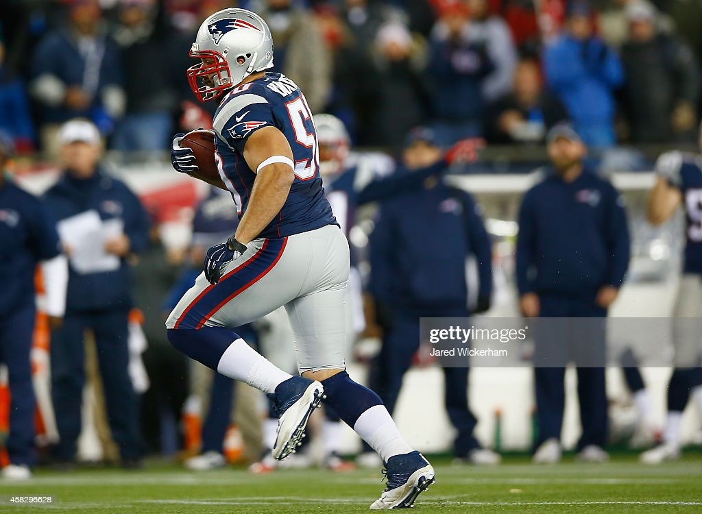 Rob Ninkovich of the New England Patriots runs with the ball after intercepting a pass during the second quarter against the Denver Broncos at...