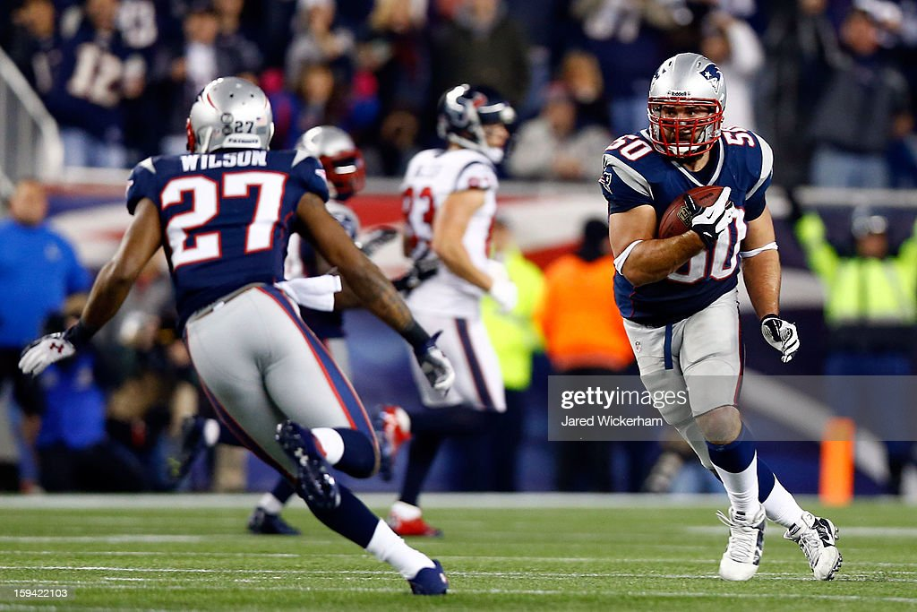 Rob Ninkovich of the New England Patriots runs with the ball after an interception against the Houston Texans during the 2013 AFC Divisional Playoffs...