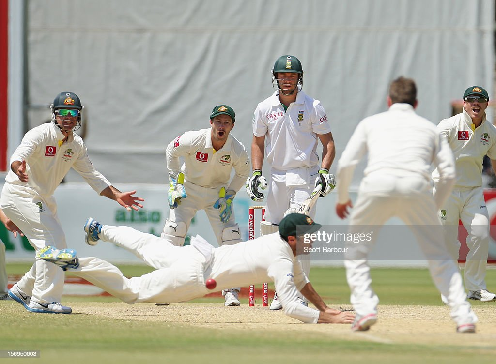 Rob Quiney of Australia dives as he attempts to take a catch as batsman AB de Villiers of South Africa looks on during day five of the Second Test Match between Australia and South Africa at Adelaide Oval on November 26, 2012 in Adelaide, Australia.