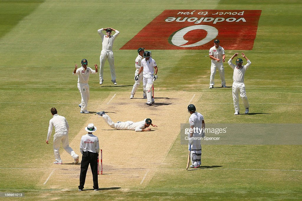 Rob Quiney of Australia lays on the pitch after attempting to catch out Faf du Plesis of South Africa off a delivery by captain Michael Clarke during day five of the Second Test Match between Australia and South Africa at Adelaide Oval on November 26, 2012 in Adelaide, Australia.
