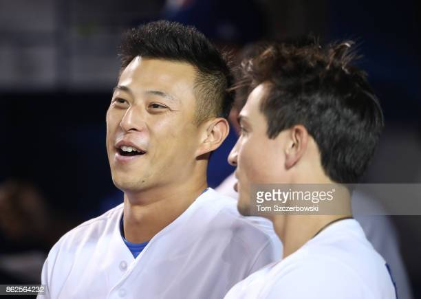 Rob Refsnyder of the Toronto Blue Jays and Darwin Barney look on from the top step of the dugout during MLB game action against the Tampa Bay Rays at...