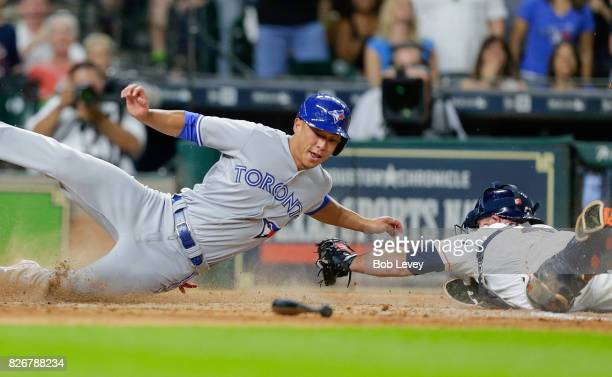 Rob Refsnyder of the Toronto Blue Jays avoids the tag of Brian McCann of the Houston Astros as he scores on a single by Ryan Goins of the Toronto...