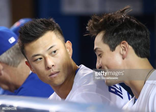 Rob Refsnyder of the Toronto Blue Jays talks to Darwin Barney as they sit on the top step of the dugout during MLB game action against the Tampa Bay...