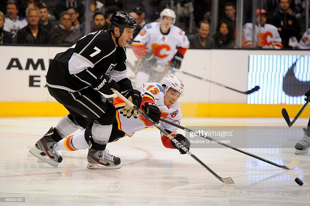 Rob Scuderi #7 of the Los Angeles Kings reaches for the puck against Mike Cammalleri #13 of the Calgary Flames at Staples Center on March 11, 2013 in Los Angeles, California.