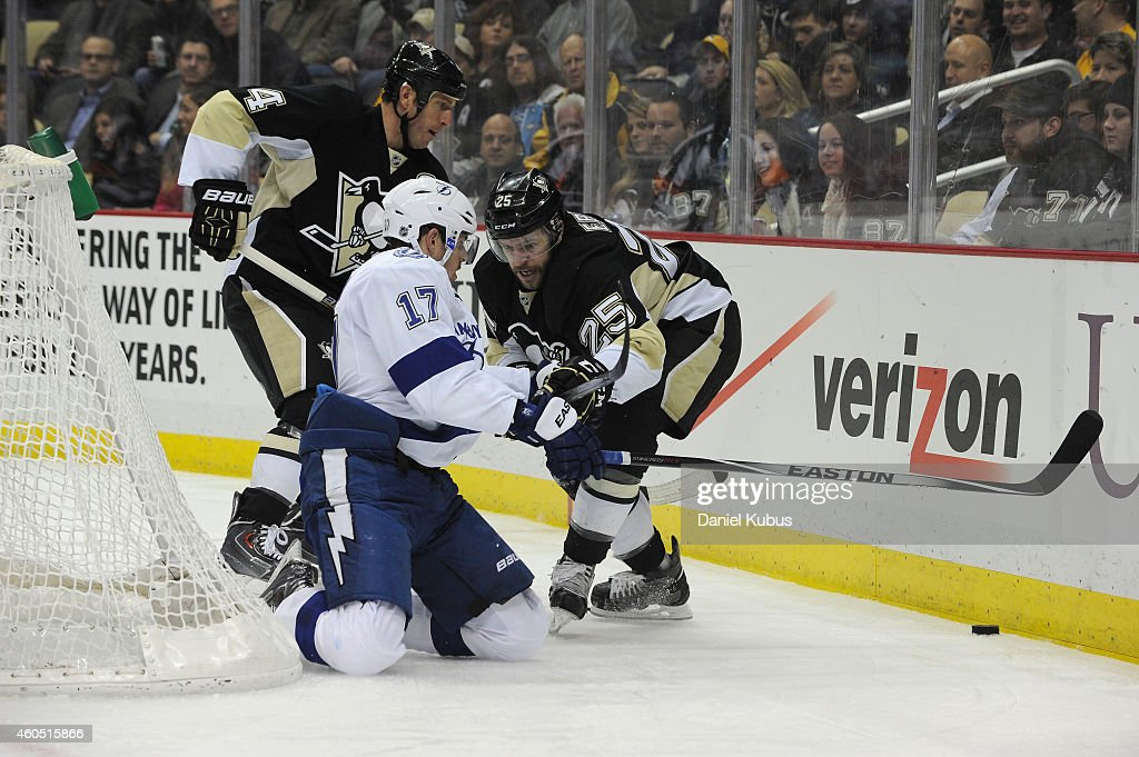 Rob Scuderi of the Pittsburgh Penguins Alex Killorn of the Tampa Bay Lightning and Andrew Ebbett of the Pittsburgh Penguins fight for a loose puck in...