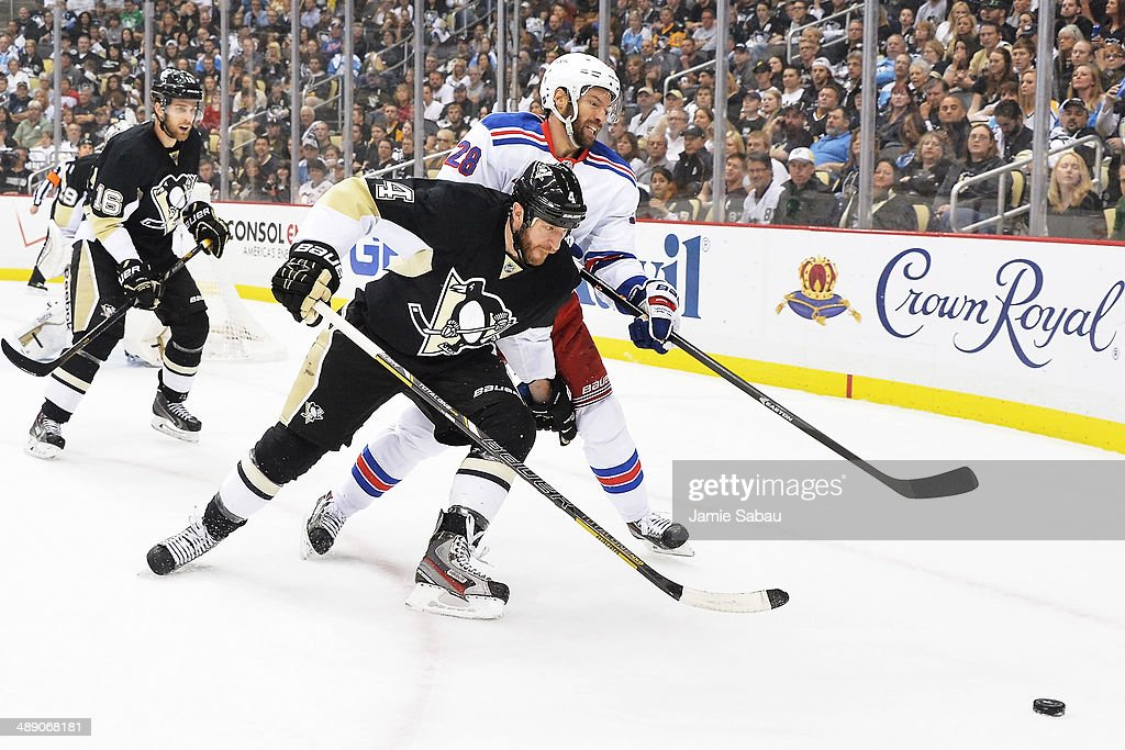 Rob Scuderi #4 of the Pittsburgh Penguins and Dominic Moore #28 of the New York Rangers battle for position while chasing down a loose puck in the first period in Game Five of the Second Round of the 2014 NHL Stanley Cup Playoffs on May 9, 2014 at CONSOL Energy Center in Pittsburgh, Pennsylvania. New York defeated Pittsburgh 5-1.