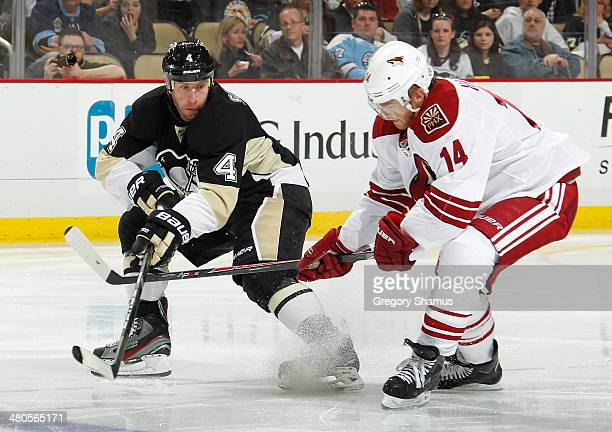 Rob Scuderi of the Pittsburgh Penguins and Jeff Halpern of the Phoenix Coyotes battle for the loose puck on March 25 2014 at Consol Energy Center in...