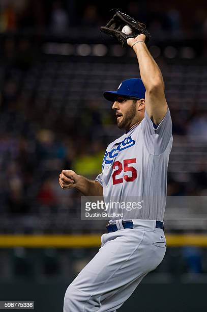 Rob Segedin of the Los Angeles Dodgers fields a fly ball in foul territory to end the third inning of a game against the Colorado Rockies at Coors...