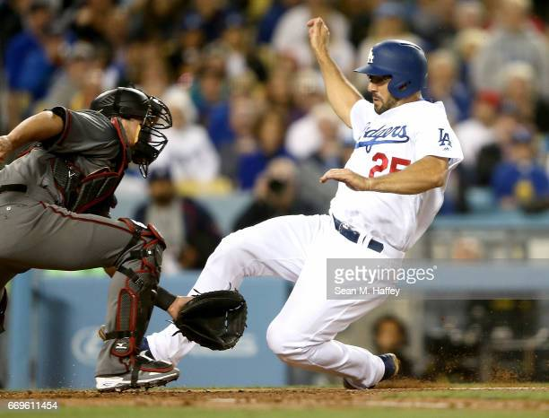 Rob Segedin of the Los Angeles Dodgers slides safely at home past the tag of Jeff Mathis of the Arizona Diamondbacks during the second inning of a...