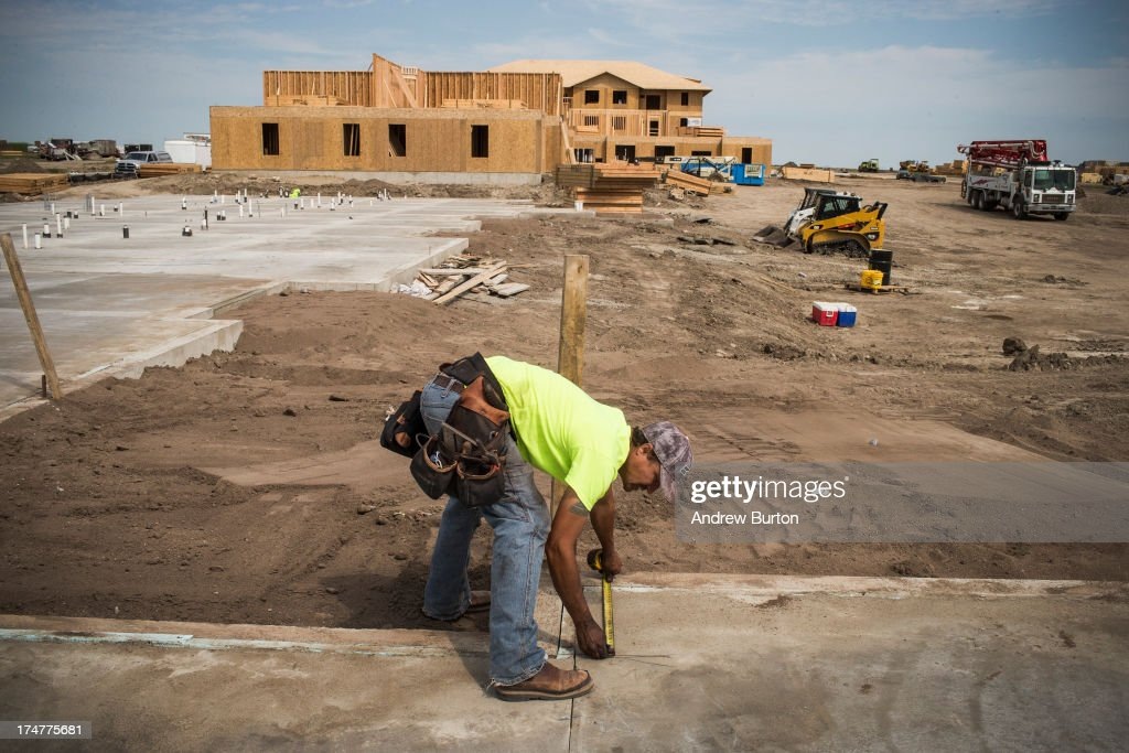 Rob Thomasson works at a residential construction site on July 28, 2013 in Watford, North Dakota. North Dakota has been experiencing an oil boom in recent years, due in part to new drilling techniques including hydraulic fracturing and horizontal drilling. In April 2013, The United States Geological Survey released a new study estimating the Bakken formation and surrounding oil fields could yield up to 7.4 billion barrels of oil, doubling their estimate of 2008, which was stated at 3.65 billion barrels of oil.