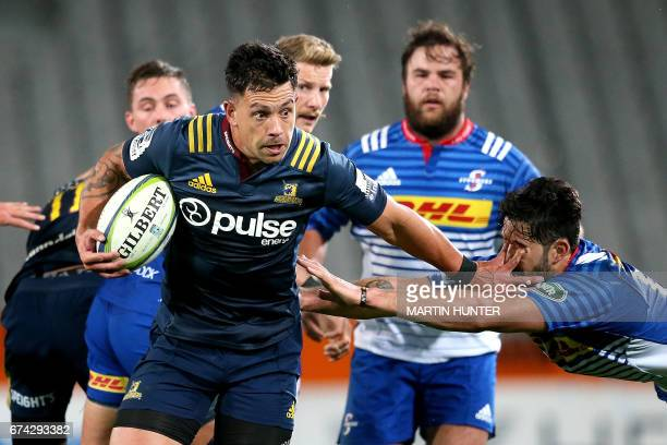 Rob Thompson of the Otago Highlanders breaks through the tackle of EW Viljoen of the Western Stormers to score a try during the Super Rugby match...
