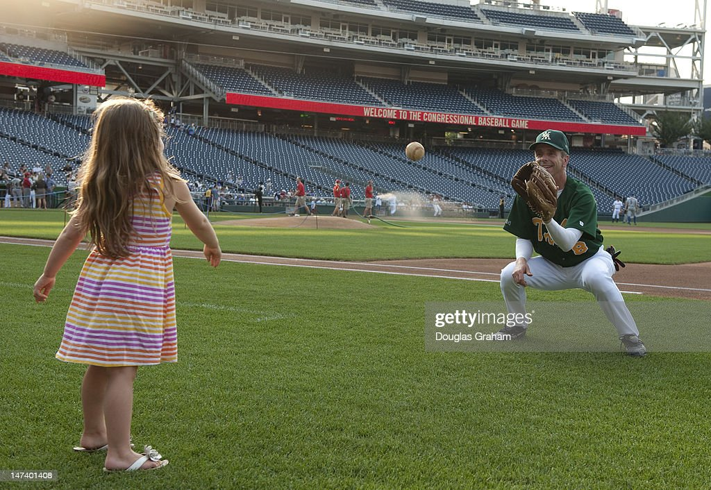 Rob Wittman, R-VA., gets a little warm-up help from his granddaughter Morgan during the 51tst Annual Roll Call Congressional Baseball Game held at Nationals Stadium, June 28, 2012.