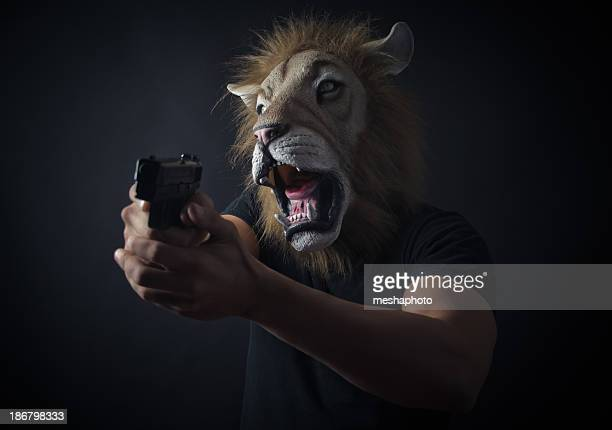 Robber in lion mask holding a gun