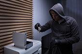 Robber Standing In Living Room Holding Flashlight