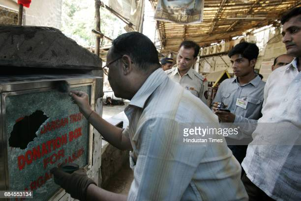 Robbery A fingerprint expert examins the donation box at Haji Ali dargah which was broken by unknown accused on early Saturday morning