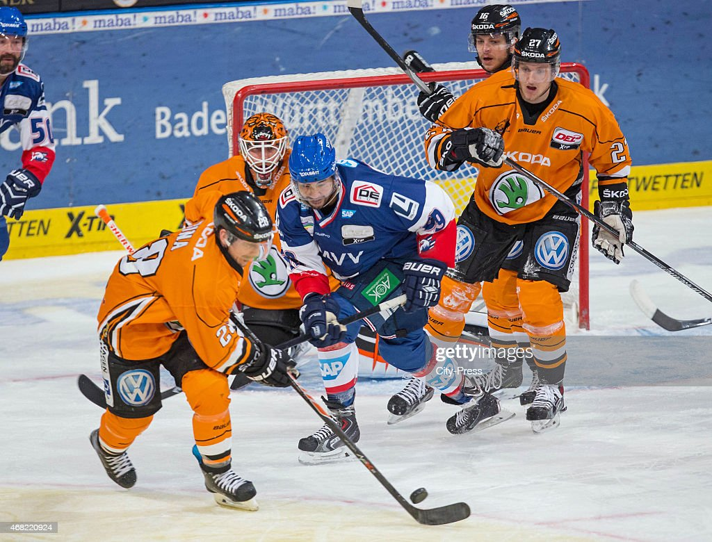 Robbie Bina of the Grizzly Adams Wolfsburg handles the puck against Brandon Yip of the Adler Mannheim during the game between Adler Mannheim and...