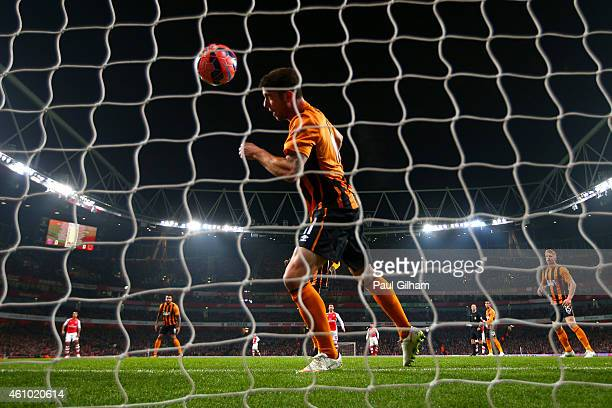 Robbie Brady of Hull City attempts in vain to block a goalbound effort from Per Mertesacker of Arsenal during the FA Cup Third Round match between...