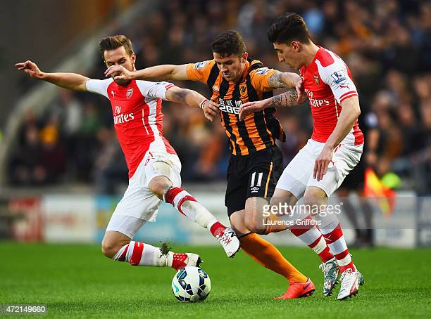 Robbie Brady of Hull City goes between Aaron Ramsey and Hector Bellerin of Arsenal during the Barclays Premier League match between Hull City and...