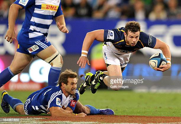 Robbie Coleman of the Brumbies skips over the tackle by Nick Groom of the Stormers during the Super Rugby round six match between DHL Stormers and...